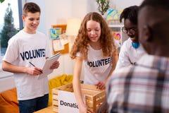 Tonåringar som arbetar i organisationen som samlar objekt för donation royaltyfri fotografi