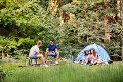 Tonåringar som campar i skogsommaraffärsföretag Arkivfoto