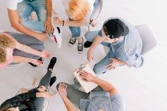 Tonåringar som sitter i cirkel Arkivfoton