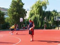 Tonåringar som spelar basket på lekplats Arkivfoto