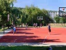Tonåringar som spelar basket på lekplats Arkivfoton