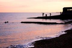 Tonåringar som spelar på solnedgången på vattenkanten Royaltyfri Bild