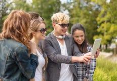 Tonåringar som tar fotoet med minnestavlaPC utanför Arkivfoto