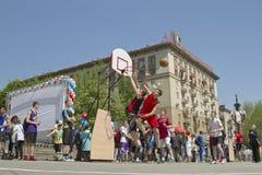 Tonåringar spelar streetball på den frilufts- asfaltjordningen Royaltyfri Bild