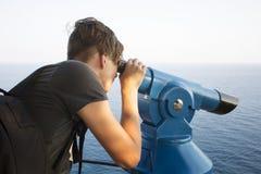 Tonåringbevakningar till och med teleskopet Royaltyfri Bild