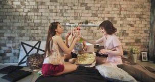 Tonåringdamer har en hem- partisleepovernatt i pyjamasdamen som kör med askar för en pizza som kommer med dem till sängen stock video