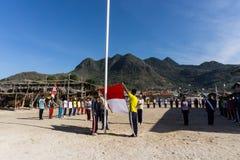 Tonåringdrev för Indonesien den oberoende dagen i den lilla ön med berget på bakgrunden royaltyfri fotografi