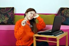 Tonåringen är trött av att använda bärbara datorn arkivbild