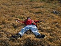 Tonåringen föll in i det tjocka gräset Fotografering för Bildbyråer