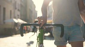 Tonåringen går med cykeln i stad arkivfilmer