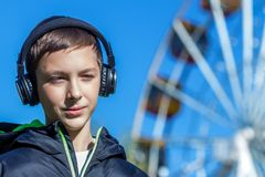 Tonåringen i ett svart omslag som lyssnar till musik med hörlurar, near munterhetpariserhjulen royaltyfri bild