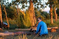 Tonåringen lägger ut ett tält bland träden på solnedgången arkivbild