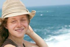 Tonåringen med en hatt ler på kameran Arkivbilder