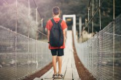 Tonåringen med en ryggsäck i bergen, en pojke korsar en bergflod på en upphängningbro arkivbild