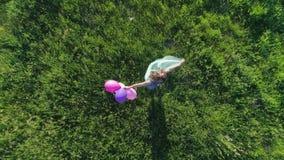 Tonåringen med ljust hår rotera med ballonger på bakgrund av grön gräsmatta på den soliga dagen, flyg- sikt arkivfilmer
