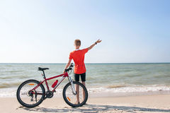Tonåringen poserar med cykeln på en bakgrund av havet royaltyfria foton
