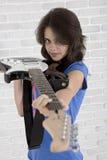 Tonåringen siktar med den elektriska gitarren som ett vapen royaltyfria bilder
