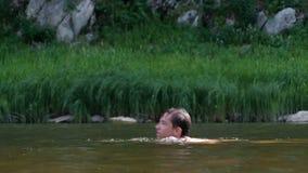 Tonåringen simmar rakt till vänstert längs floden förbi vasserna bl?a pojkeskrivbordflickor ser sittande surfa f?r havet Semester lager videofilmer
