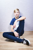 Tonåringen sitter på ett golv i rummet Arkivbild