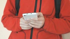 Tonåringen som inomhus rymmer en vit mobiltelefon lager videofilmer