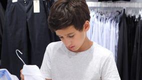Tonåringen som ser kläder i innegrej, shoppar ultrarapid 4k lager videofilmer