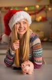 Tonåringflicka i den santa hatten med spargrisen Royaltyfri Foto