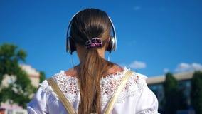 Tonåringflicka i den vita klänningen med lång hårresor runt om stad mot den blåa himlen långsam rörelse En ung flicka går arkivfilmer