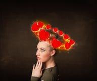 Tonåringflicka med hjärtaillustrationer som circleing runt om hennes huvud Arkivbild