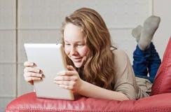Tonåringflicka med minnestavladatoren royaltyfri fotografi