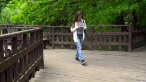 Tonåringflicka som använder mobiltelefonen på träbron Ungt tonårigt smsande meddelande på att gå för smartphone Rörelsekamera stock video