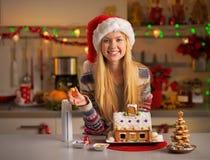 Tonåringflicka som dekorerar julkakahuset Arkivfoto