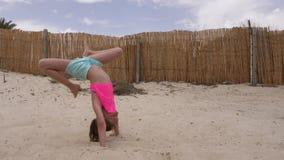 Tonåringflicka som gör akrobatiskt jippo på den tomma stranden för sand långsam rörelse stock video