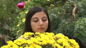 Tonåringflicka som luktar blommor stock video