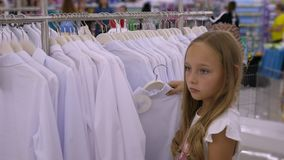 Tonåringflicka som väljer den vita blusen i klädlager Mode och shopping lager videofilmer