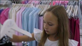 Tonåringflicka som väljer kläder i modelager Mode- och shoppingbegrepp arkivfilmer