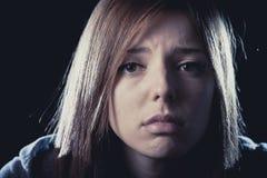 Tonåringflickan i spänning och smärtar lidandefördjupningen som är ledsen och som är förskräckt i skräckframsidauttryck Arkivfoton