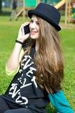 Tonåringflickan med hatten parkerar in samtal på telefonen Royaltyfria Foton