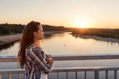 tonåringflickan med lockigt hår i livsstil beklär anseende nära en räcke på bron som ser soluppgång royaltyfri bild