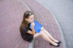Tonåringflickan sitter på momenten med en mapp i henne händer arkivfoton