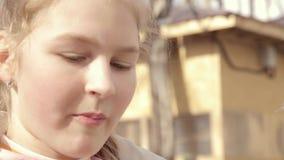 Tonåringflickan som äter en munk i ett utomhus-, parkerar stock video