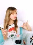 Tonåringflickan som blåser på målat, spikar Arkivfoton