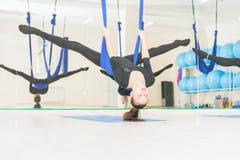 Tonåringflickan som gör sträckning och, tvinnar, flyg- yoga Arkivbild