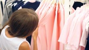 Tonåringflickan som ser kläder i innegrej, shoppar ultrarapid 4k stock video