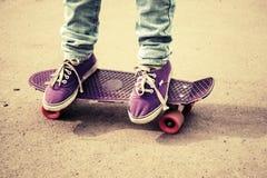 Tonåringfot i jeans och deckare på skateboarden Royaltyfri Foto