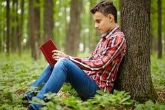 Tonåringläsning en boka royaltyfri foto