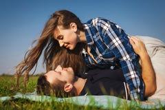 Tonåringlögn på gräset flickaöverkant av grabben Royaltyfri Foto