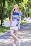 Tonåringlivsstilbegrepp Lycklig le Caucasian blond tonåringflicka som utomhus poserar med Longboard royaltyfri foto