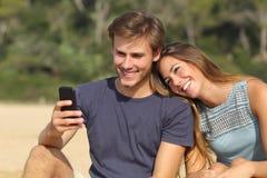Tonåringpar som delar socialt massmedia på den smarta telefonen royaltyfri fotografi