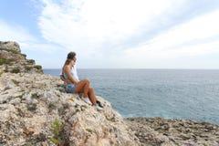Tonåringpar som ser horisonten på en klippa Arkivfoto