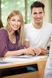 Tonåringpar som tillsammans studerar Arkivbild